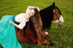 Mulher bonita com um cavalo no campo Menina em uma exploração agrícola com a Imagens de Stock Royalty Free