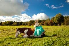 Mulher bonita com um cavalo no campo Menina sobre Imagem de Stock
