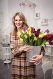 A mulher bonita com um ramalhete das tulipas floresce em uma cubeta do metal Fotos de Stock