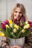 A mulher bonita com um ramalhete das tulipas floresce em uma cubeta do metal Imagens de Stock