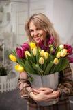 A mulher bonita com um ramalhete das tulipas floresce em uma cubeta do metal Fotos de Stock Royalty Free