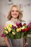 A mulher bonita com um ramalhete das tulipas floresce em uma cubeta do metal Foto de Stock