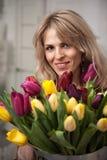 A mulher bonita com um ramalhete das tulipas floresce em uma cubeta do metal Imagem de Stock Royalty Free