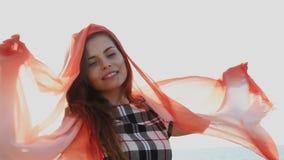 A mulher bonita com um xaile vermelho está fundindo no vento filme