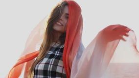 A mulher bonita com um xaile vermelho está fundindo no vento video estoque