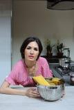 Mulher bonita com uma bacia de massa que cozinha o comensal na cozinha imagem de stock royalty free