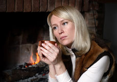 Mulher bonita com uma caneca perto de uma chaminé imagens de stock royalty free