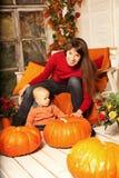 Mulher bonita com uma criança no pátio de entrada coberto com au das abóboras Imagem de Stock Royalty Free
