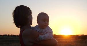 Mulher bonita com uma criança que aprecia a vista rústica efervescente no por do sol imagens de stock