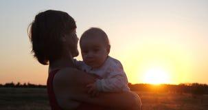 Mulher bonita com uma criança que aprecia a vista rústica efervescente no por do sol imagem de stock royalty free