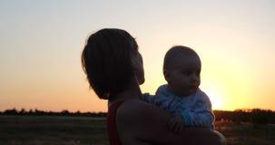Mulher bonita com uma criança que aprecia a vista rústica efervescente no por do sol video estoque