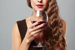 Mulher bonita com vinho vermelho de vidro Penteado encaracolado Fotografia de Stock Royalty Free