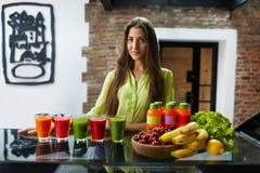 Mulher bonita comendo saudável com Juice Smoothie Indoors fresco Fotografia de Stock Royalty Free