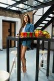 Mulher bonita comendo saudável com Juice Smoothie Indoors fresco Imagem de Stock