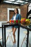 Mulher bonita comendo saudável com Juice Smoothie Indoors fresco Fotografia de Stock