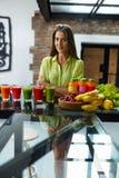 Mulher bonita comendo saudável com Juice Smoothie Indoors fresco Imagem de Stock Royalty Free