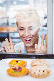 Mulher bonita confundida que olha uma torta do fruto através do vidro Imagem de Stock