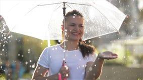 Mulher bonita consider?vel que olha acima do c?u e para levantar a m?o para verificar se a parada da chuva que sorri e para fecha filme