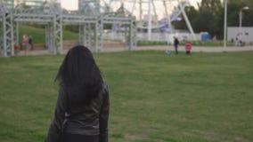 A mulher bonita corre e gerencie ao redor no fundo do parque ensolarado do verão filme