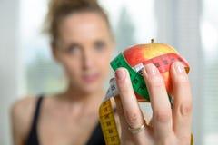 Mulher bonita da aptidão com medida da fita e a maçã imagens de stock