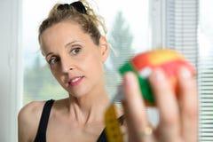 Mulher bonita da aptidão com medida da fita e a maçã fotografia de stock royalty free