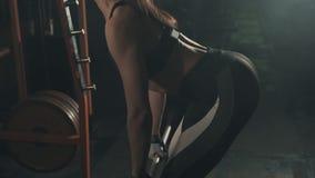 Mulher bonita da aptidão que faz o treinamento do barbell no gym no movimento lento video estoque