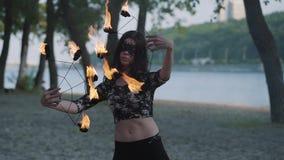 Mulher bonita da benevolência nova do retrato na máscara que executa uma mostra com a posição da chama no riverbank na frente das video estoque