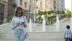 Mulher bonita da elegância que usa o telefone no fundo da fonte filme
