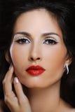 A mulher bonita da forma com composição brilhante toca em sua pele perfeita na face foto de stock royalty free