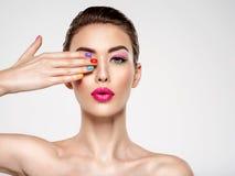 Mulher bonita da forma com pregos coloridos Menina branca atrativa com tratamento de mãos multicolorido fotos de stock royalty free