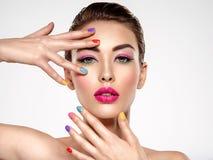 Mulher bonita da forma com pregos coloridos Menina branca atrativa com tratamento de mãos multicolorido fotografia de stock
