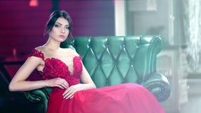 Mulher bonita da forma do tiro médio que veste o vestido glamoroso que flerta e que levanta olhando a câmera filme