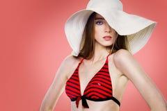Mulher bonita da forma no chapéu branco e no roupa de banho vermelho fotografia de stock