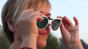 Mulher bonita da Idade Média que sorri nos óculos de sol no movimento lento video estoque