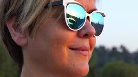 Mulher bonita da Idade Média que sorri nos óculos de sol no movimento lento filme