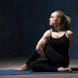 Mulher bonita da ioga que faz o meio senhor da pose dos peixes foto de stock