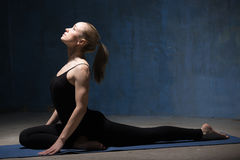 Mulher bonita da ioga que senta-se na única pose do pombo imagem de stock royalty free