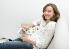 Mulher bonita da jovem mulher com uma tabuleta no sofá imagem de stock