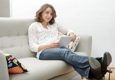 Mulher bonita da jovem mulher com uma tabuleta no sofá fotografia de stock royalty free