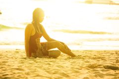 Mulher bonita de Ásia que senta-se na areia da praia fotografia de stock