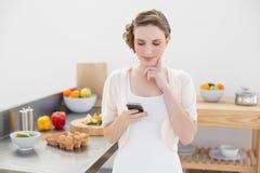 Mulher bonita de pensamento que usa seu smartphone que está na cozinha Fotos de Stock