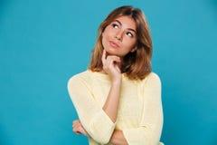 Mulher bonita de pensamento sobre o fundo azul fotos de stock royalty free