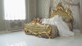 Mulher bonita de riso nova no traje branco da bola do vintage que corre e que salta à cama dourada enorme filme