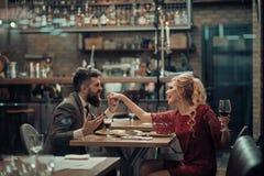 Mulher bonita de sedução que olha seu amante com vidro de vinho Tendo a conversa romântica imagens de stock