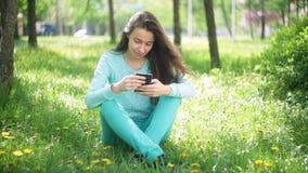 Mulher bonita de sorriso do turista dos jovens que relaxa no parque de florescência da mola com telefone vídeos de arquivo