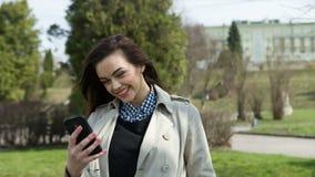 Mulher bonita de sorriso que texting com seu telefone video estoque
