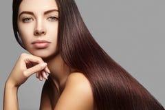 Mulher bonita de Yong com cabelo marrom por muito tempo reto Modelo de forma 'sexy' com penteado liso do brilho Tratamento da que imagens de stock