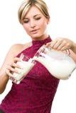 A mulher bonita derrama para fora o leite no vidro Imagens de Stock Royalty Free