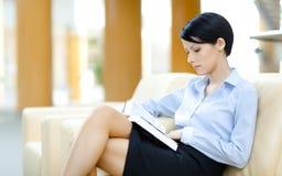 A mulher bonita descansa no sofá com livro fotografia de stock royalty free