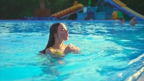Mulher bonita do ajuste que relaxa na piscina Ela mergulho na água filme
